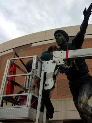"""Michigan State University utility worker Tracy Harris was hard at work Thursday cleaning yellow and blue paint off the statue of Earvin """"Magic"""" Johnson in front of the Breslin Center. It's the first time the statue has been vandalized."""