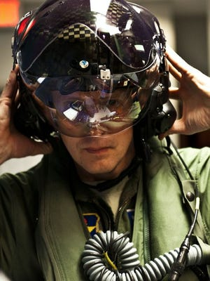 Lt. Col. Eric Smith, from the 58th Fighter Squadron, straps on his F-35 helmet in this 2012 photo. Smith was the first Air Force pilot qualified to fly the F-35. Officials believe the advanced helmets will provide pilots with faster access to tactical information and a better visual of what's on the ground.