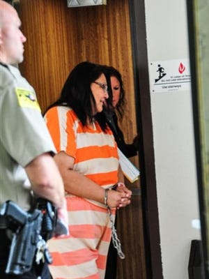 In this photo taken on Tuesday, Aug. 18, 2015, Janice Howe exits the elevator at the courthouse after a hearing, in Pierre, S.D. Howe, who lived for more than a decade with an outstanding arrest warrant, pleaded guilty to a felony for violating election law.