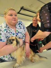 Volunteers Olivia Punke, left, holds a dog while getting
