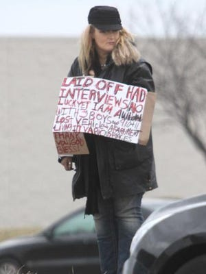A woman panhandles near Glenstone Avenue in March 2014. The American Civil Liberties Union has sued Springfield over its panhandling ordinance.