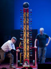 Step right up: 'Mythbusters' co-host Jamie Hyneman, left, tests his strength on the High Striker as Adam Savage watches.