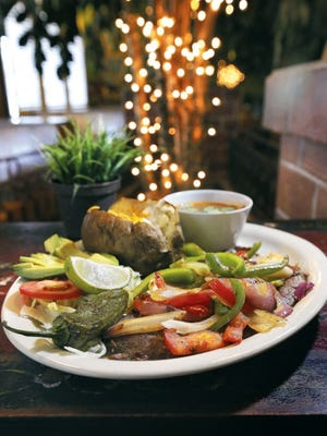 The Tampiquena Steak from El Parque Restaurant at Las Palmas Marketplace, 1319 George Dieter, is served with grilled peppers and onion and a baked potato.