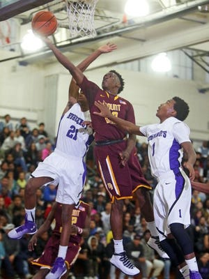 Mount Vernon's Marco Morency is pressured by New Rochelle's Justin Dior Watson and Chad Williams, Jr. during a varsity basketball game at New Rochelle High School Jan. 15, 2015. Mount Vernon lost a double digit lead, but hung on to defeat New Rochelle 61-57.