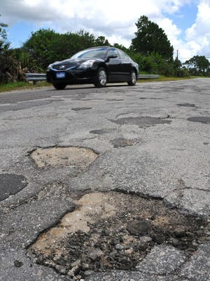 A car navigates pothole-marred Lowry Boulevard in southern Palm Bay in this 2016 file photo.