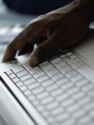 Hand on laptop computer keyboard.