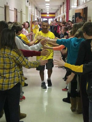 Fort Gratiot Middle School custodian Ray Ledezma walks down the halls high-fiving students a week before taking on the Boston Marathon.