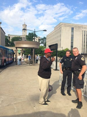Sgt. Larry Hansen and Officer Mike Evans speak with a passerby at the bus station.