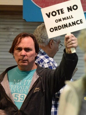 A member of the public holds a sign against an ordinance that would have permitted redevelopment at Monmouth Mall