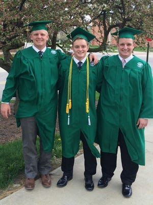 Matt, Jake and Chris Smith from Midland pose in their caps and gowns at Michigan State University on Thursday, May 5, 2016. The triplets graduate Saturday.