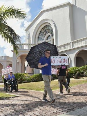 Members and supporters of the Concerned Catholics of Guam and Laity Forward Movement hold a protest against Archbishop Anthony Apuron at Dulce Nombre de Cathedral Basilica in Hagatna on June 19.