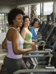 Women exercising on treadmills at a gym.