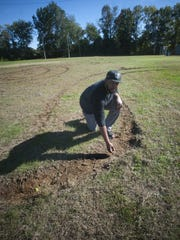 Camden Raiders coach Robert Kelley shows some of the damage to the field outside Malandra Hall last week.