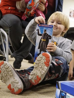 A child receives a toy from Toys for Tots at a 2015 event in Livonia.