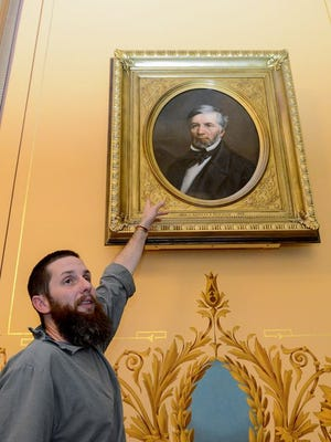 Joshua Adam Risner describes the handmade frame around his portrait of former Michigan Gov. Kinsley Bingham hanging in the Capitol Building on Nov. 10, 2016, in Lansing.