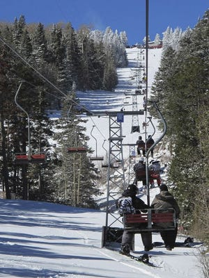 In this March 11, 2012, file photo snowboarders ride the chairlift at Sandia Peak Ski Area near Albuquerque, N.M. Forecasters are warning that the state could be in for more warm, dry weather as ski resorts gear up for openings later this month.