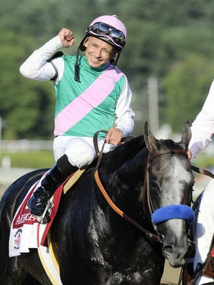 In this Aug. 27, 2016, file photo, Jockey Mike Smith celebrates aboard Arrogate after winning the Travers Stakes horse race at Saratoga Race Course in Saratoga Springs, N.Y.