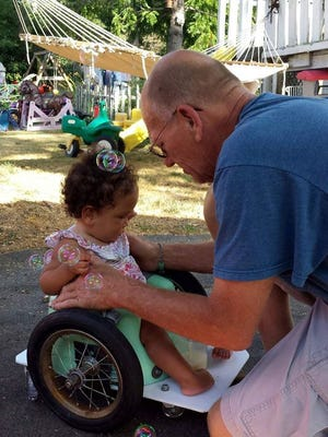 Marty Parzynski helps his niece Bella into her brand new Bella's Bumba chair last July. It took Bella only a week or two to learn how to maneuver it by herself.
