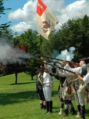 Re-enactors fire muskets during a past Independence