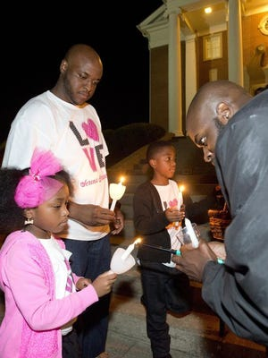 """Randy Brent, center, and his two children Siara Joy, left, and Randy Jamai, right center, have candles of remembrance lit before starting the Capital Area Healthy Start Coalition """"Walk to Remember."""""""