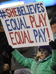 A girl holds up a sign for equal pay for the U.S. women's