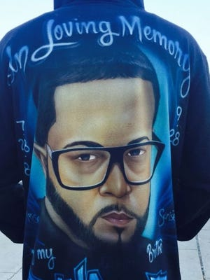 A family member wears a jacket with a memorial to Jose Franco, who was shot during a robbery in 2015.