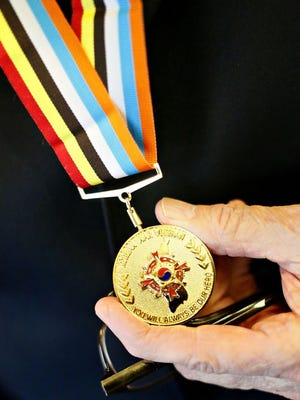 """Major Harold Borror, 87, holds a medal naming him an """"Ambassador for Peace"""", presented to him by the Republic of Korea, at the Salvation Army in York City, Wednesday, Nov. 9, 2016. Dawn J. Sagert photo"""