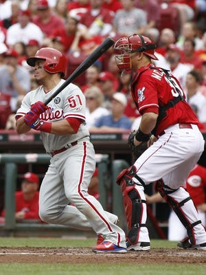The Phillies' Carlos Ruiz (51) hits a single off Cincinnati Reds pitcher Homer Bailey during the fourth inning Sunday in Cincinnati. Reds catcher Devin Mesoraco watches at right.