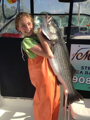 Liane Lopez holds the 32-pound striped bass she caught while fishing with Capt. Raymond Lopez on the Miss Liane out of Forked River.