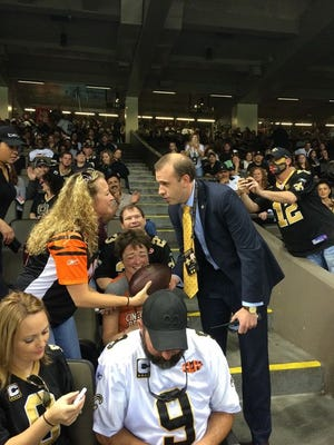 Christa Barrett receiving a ball from a Saints representative during Sunday's game.