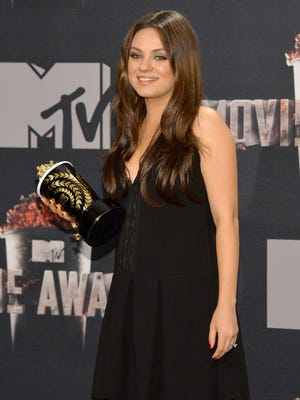 Actress Mila Kunis poses with the best villain award in the press room during the 2014 MTV Movie Awards at Nokia Theatre L.A. Live on April 13, 2014 in Los Angeles.