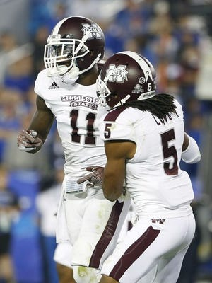 Mississippi State safety Kivon Coman (11) and Jamerson Love celebrate during their team's win at Kentucky.