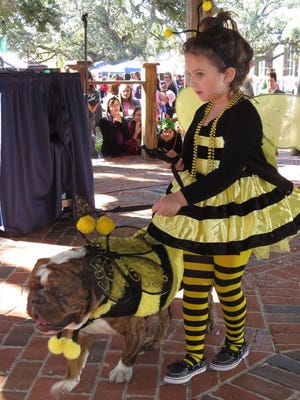 Dressed as bumblebees, Sofia Stanley and her dog, Atlas, buzz past the judges' table during a costume contest during Barktoberfest.