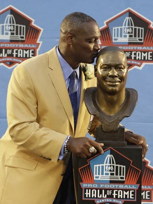 Hall of Fame Inductee Derrick Brooks kisses his bust during the 2014 Pro Football Hall of Fame Enshrinement Ceremony at the Pro Football Hall of Fame on Saturday.