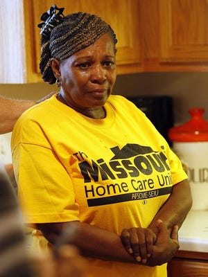Cartessie Johnson tearfully speaks about the financial struggles of being a low paid home health care worker in the kitchen of Ulysses Calloway of Springfield on August 28, 2014.