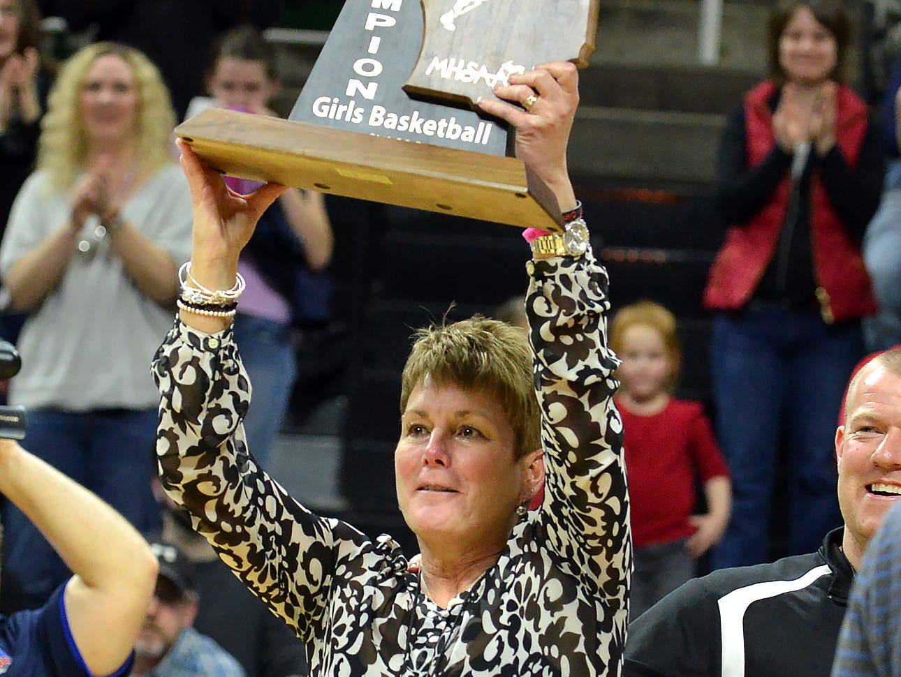 Marshall head coach Sal Konkle shows of the 2016 MHSAA Class B State Championship trophy at the Michigan State University Breslin Center.