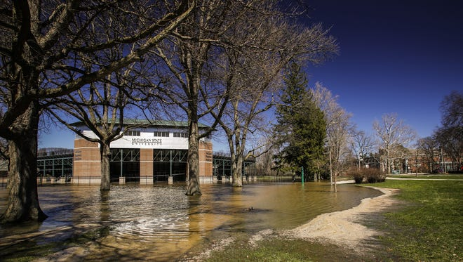 High water levels in the Red Cedar River have flooded areas around McLane Stadium at Kobs Field on the campus of Michigan State University Friday, April 7, 2017.