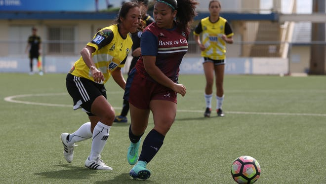 Bank of Guam Lady Strykers' Jinae Teria checks over her shoulder before she attempts to make a move around the defense of NAPA Lady Rovers' Kyung Shipman in an opening week match of the 2017 Bud Light Women's Soccer League Fall season Sunday at the Guam Football Association National Training Center. The Lady Rovers won 2-1.