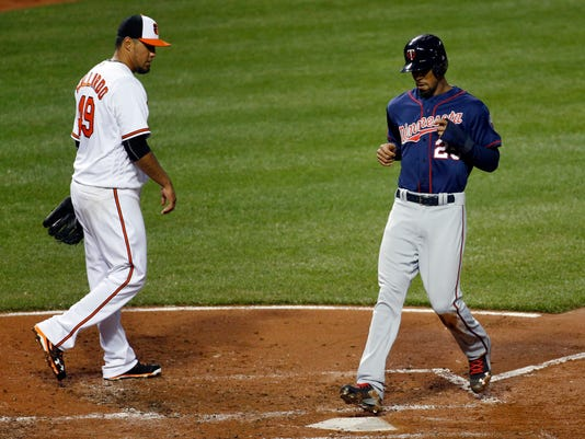 Minnesota Twins' Byron Buxton, right, crosses home plate in front of Baltimore Orioles starting pitcher Yovani Gallardo for a run on a sacrifice fly ball by Joe Mauer in the third inning of a baseball game in Baltimore, Wednesday, April 6, 2016. (AP Photo/Patrick Semansky)