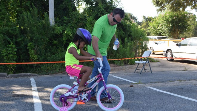 "FILE -- David Laborde (right) of the Laborde Earles Law Firm helps Marlexia Sanders navigate the course on her new bike during the ""Bike It Forward"" event in 2015."