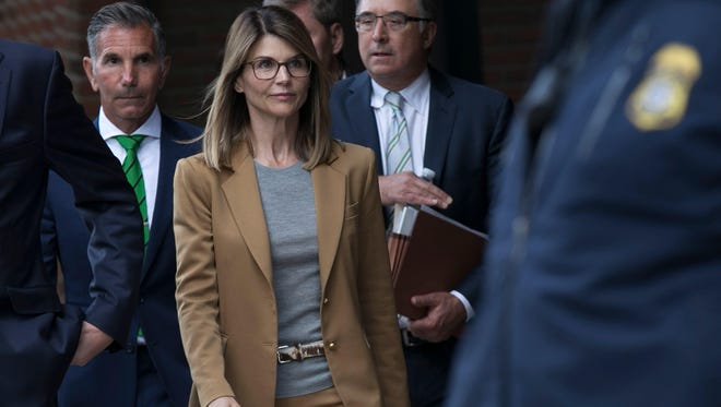 Lori Loughlin (C) and her husband Mossimo Giannulli (L) leave the John J Moakley Federal Court House after facing charges in a nationwide college admissions cheating scheme in Boston.