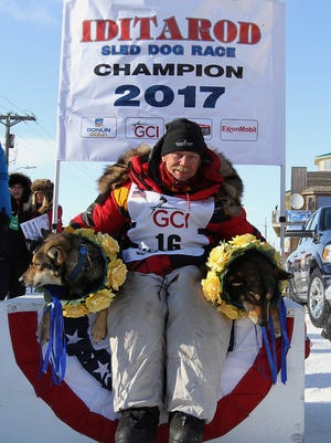 Iditarod champion Mitch Seavey of Sterling, Alaska, poses with his lead dogs Pilot, left, and Crisp under the Burled Arch after winning the 1,000-mile Iditarod Trail Sled Dog Race.