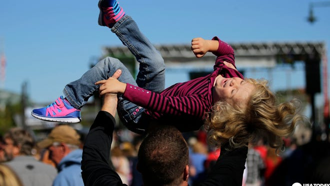 Michael Priscal of Neenah lifts his daughter, Haley, on Saturday as they listen to Ask Your Mother during Octoberfest in downtown Appleton.