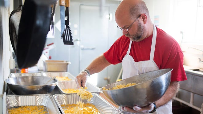 Erik Wilkinson works on the mac and cheese as him and others prepare the annual Haven of Rest Thanksgiving meal on Tuesday, November 22, 2016 in Belton.