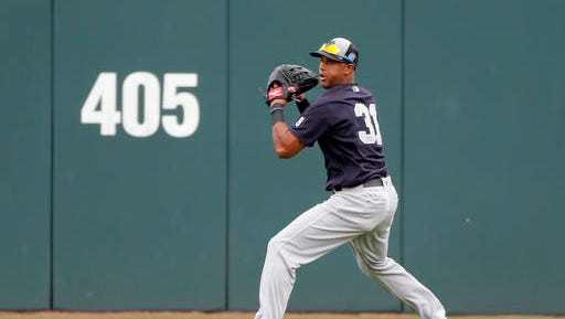 New York Yankees center fielder Aaron Hicks prepares to make a throw to third after fielding a fly-out by Minnesota Twins' Eduardo Escobar in the fourth inning of a spring training baseball game, Sunday, March 20, 2016, in Fort Myers, Fla. Hicks threw out the Twins' Eddie Rosario who was trying to advance to third on the fly out.