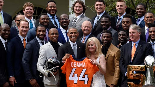 President Barack Obama, center, standing next to Annabel Bowlen, wife of Broncos owner Pat Bowlen, holds up a Denver Broncos team football jersey, as he welcomes the Super Bowl Champions during a ceremony in the Rose Garden of the White House in Washington, Monday, June 6, 2016, to honor the team and their Super Bowl 50 victory.(AP Photo/Susan Walsh)