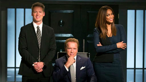 """This image released by NBC shows, from left, Patrick Knapp Schwarzenegger, Arnold Schwarzenegger and Tyra Banks from """"The New Celebrity Apprentice,"""" in Los Angeles. Schwarzenegger is the latest victim of a Donald Trump Twitter attack. The president-elect took time Friday to note that the """"Terminator"""" star was """"swamped"""" in his """"Celebrity Apprentice"""" debut """"by comparison to the ratings machine, DJT.""""  Trump is right about the ratings, using the comparison he set up. His Jan. 4, 2004 debut on the reality show drew 18.49 million viewers, and Schwarzenegger's Monday bow as host was seen by 4.95 million. However, television shows almost always fade in popularity with time, and live viewership in general is down in an on-demand world."""