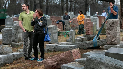 Sally Amon and her son Max Amon of Olivette, Mo., react as they saw toppled gravestone of her grandmother Anna Ida Hutkin at Chesed Shel Emeth Cemetery in University City, a suburb of St. Louis on Tuesday, Feb. 21, 2017. Vandals have damaged or tipped over as many as 200 headstones at the Jewish cemetery in suburban St. Louis, leaving the region's Jewish community shaken and anxious. (Robert Cohen/St. Louis Post-Dispatch via AP)