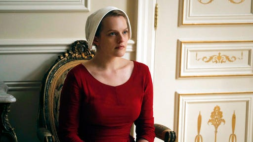 "This image released by Hulu shows Elisabeth Moss as Offred in a scene from, ""The Handmaid's Tale."" The series has won a second season from Hulu.  ""The Handmaid's Tale,"" adapted from the acclaimed Margaret Atwood novel and starring Elisabeth Moss, premiered April 26 as Hulu's biggest-ever series debut."