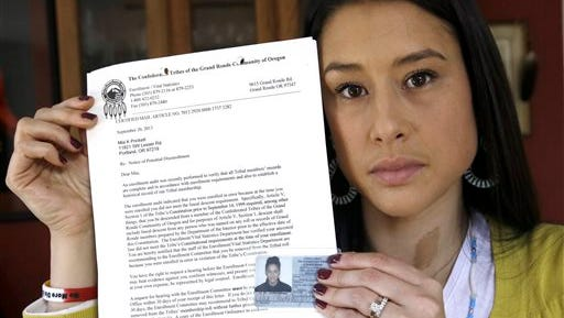 FILE - This Jan. 16, 2014 file photo shows Mia Prickett holding her Confederated Tribe of Grande Ronde enrollment card along with a recent notice of potential disenrollment from the tribe in Portland, Ore.  An Oregon woman says 86 members of her family have been disenrolled from an American Indian tribe that operates the state?s largest tribal casino. (AP Photo/Don Ryan, file)